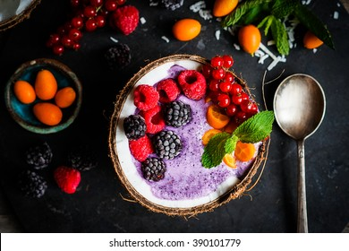 Berry smoothie with berries in coconut on rustic background