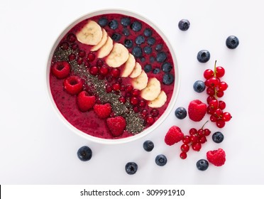 berry smoothie bowl with chia seeds, bananas, blueberries, currant and raspberries on white background