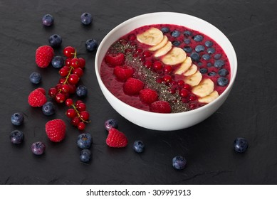 berry smoothie bowl with chia seeds, bananas, blueberries, currant and raspberries on black slate