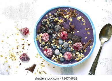 Berry smoothie with chocolate and oats in a blue bowl over light slate background.Top view.