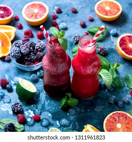 Berry smoothie with oranges and mint, healthy vitamin drink in bottles, refreshing juicy cocktail, square image
