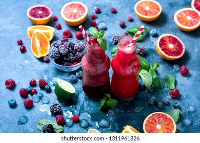 Berry smoothie with oranges and mint, healthy vitamin drink in bottles, refreshing juicy cocktail