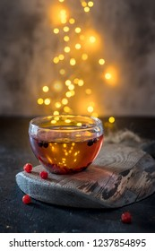 Berry tea in a glass transparent cup on wooden board with light bokeh in a background. Warm christmas drink.