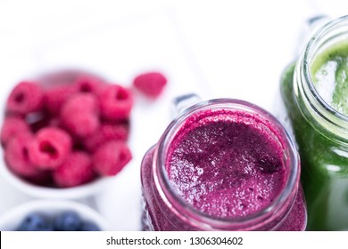 Berry and vegetables fresh smoothie in glass jars, top view with copy space