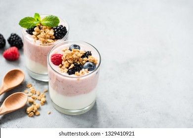 Berry yogurt with fresh berries and granola in jar. Greek yogurt, healthy breakfast parfait in glass cup. Copy space for text