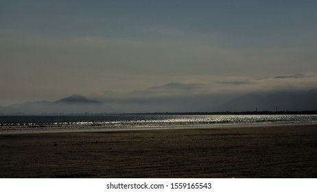 BERTIOGA, SAO PAULO,BRAZIL - Dark sandy strip with sparkling water sea and misty mountain range background.