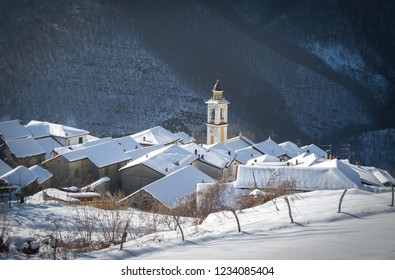 Bertone (Ottone), Piacenza, Italy - January 2013: Scenic winter view of picturesque quaint Italian village, church bell tower and fresh snow on rooftops. Photos with Snow