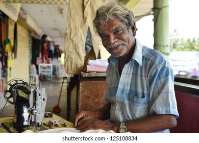BERUWALA, SRI LANKA - NOVEMBER 13:  man sewing in a small tailor shop, industrial sewing machine on November 13, 2012 in Beruwala, Sri Lanka. Sri Lankan private sewing industry.