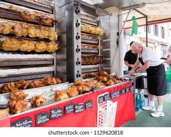 besancon, france, 10 june 2018: vendor sells golden brown chickens on grill on market in french town of besancon