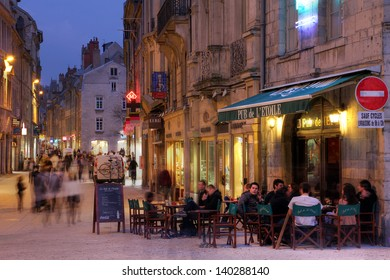 BESANCON, FRANCE - MARCH 24: Evening atmosphere along the Grand Rue in the city center of Besancon, France on March 24, 2012. On the right, Pub de L'Etoile, crowded with customers.