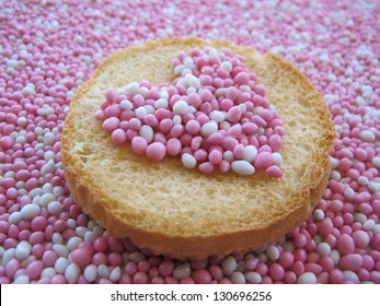 Beschuit met muisjes, traditional Dutch treat at the birth of a baby girl. Heart-shape sprinkled with pink and white anise seeds on a biscuit rusk