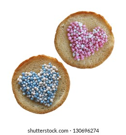 Beschuit met muisjes, traditional Dutch treat at the birth of a baby girl and boy. Two biscuit rusks with blue, pink and white anise seed sprinkles in heart-shape, isolated on white background.