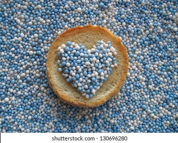 Beschuit met muisjes, traditional Dutch treat at the birth of a baby boy. Top view heart-shape on biscuit rusk and background sprinkled with blue and white anise seeds.