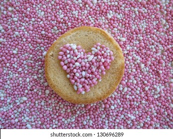 Beschuit met muisjes, traditional Dutch treat at the birth of a baby girl. Top view heart-shape on biscuit rusk and background sprinkled with pink and white anise seeds.