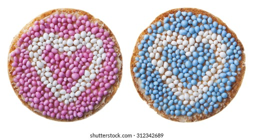 'Beschuit met muisjes', a traditional treat to celebrate the birth of a child in The Netherlands. Decorated with a heart, pink for a girl, blue for a boy. Isolated on white.