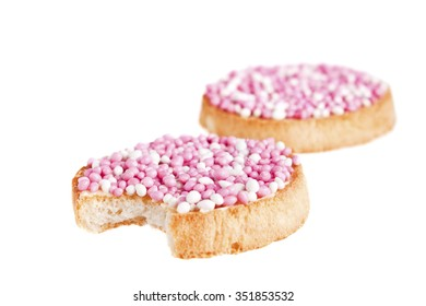 'Beschuit met muisjes', a traditional treat to celebrate the birth of a child in The Netherlands. Pink for a girl. Isolated on white, shallow depth of field.