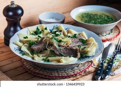 beshbarmak from beef, square-shaped pasta, fried onions and parsley