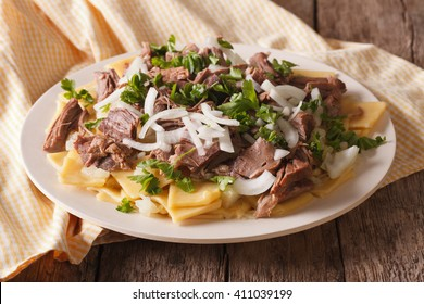 Beshbarmak dish: noodles with lamb and onion close-up on a plate on the table. horizontal