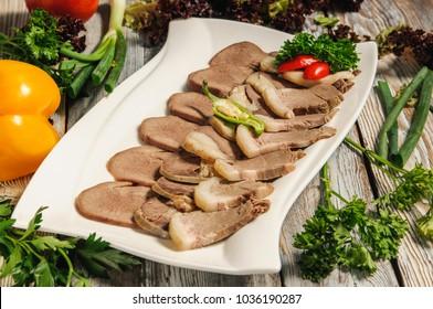 Beshbarmak - Kazakh national dish on a carved wooden platter. Festive table
