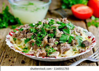 Beshbarmak national kazakh dish - egg noodles with boiled meat, onion and cilantro greens served with broth in bowl on wooden table