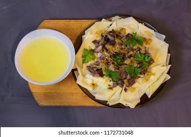 beshbarmak, a traditional Kazakh Asian dish on a gray background