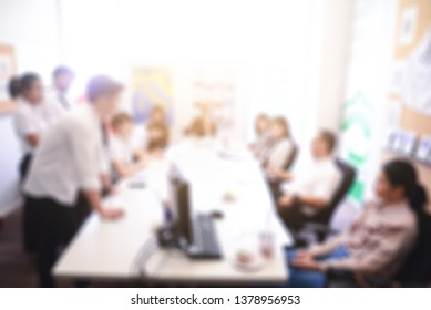 Beside blurry many students is presentation project of assignment to professor in the meeting room at university.
