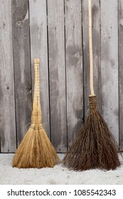 Besom and broom on the background of wooden wall