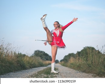 Bespectacled Blonde Teen Majorette Girl Twirling Baton Outdoors in Red Dress