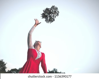 Bespectacled Blonde Teen Majorette Girl with Pom-poms Outdoors in Red Dress