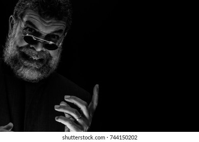 A bespectacled crazy-looking bearded old man laughs in a sinister way while he signals to us in Halloween.