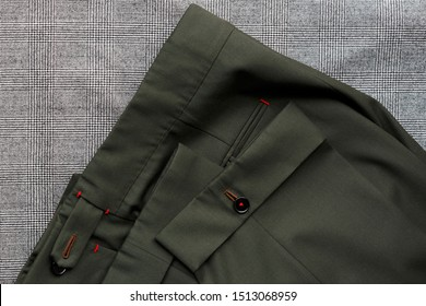 Bespoke rifle-green pants, details. Close-up view.