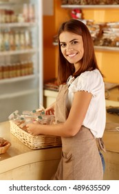Best bakery in town. Vertical shot of a beautiful young woman putting a basket with cookies on a counter at her bakery shop