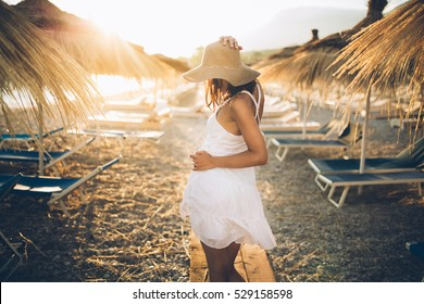 Best beach vacation destination.Beautiful sunset sand beach getaway.Stylish wear on the beach,vacation traveling concept.Stylish young woman on the beach in white dress and straw hat.Honeymoon
