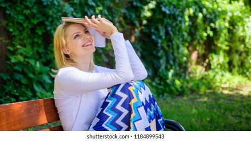 Best book ever. Woman dreamy smiling reading book in garden. Girl sit bench relaxing with book, green nature background. Lady pretty bookworm dreamy read book outdoors sunny day.