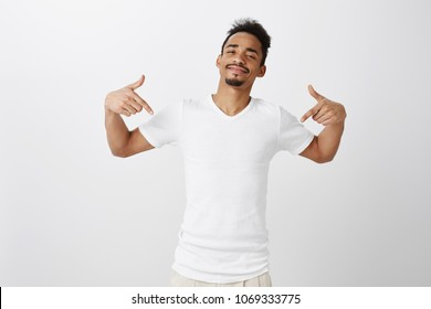 Best boyfriend in world. Studio portrait of confident dark-skinned male snob with beard and afro haircut, standing in cool satisfied pose, pointing at t-shirt or copy space, standing over gray wall