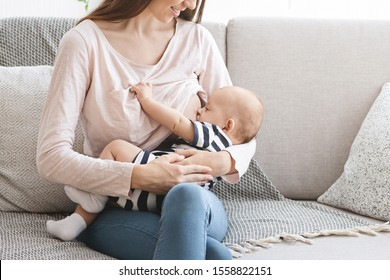 Best Breastfeeding Positions Concept. Young woman feeding her newborn baby with breast milk while sitting on couch at home, closeup
