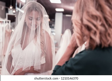 Best bride. Nice young woman smiling while standing in a beautiful wedding dress