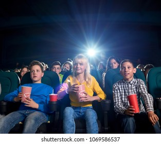Best briends enjoying film in modern cinema, sitting in comfortable chairs. Youth eating popcorn and drinking fizzy drinks. Project light source. Concept of entertainment and cinematography.