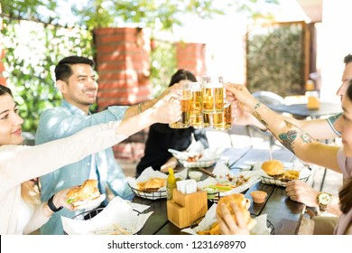 Best buddies toasting beer glasses while enjoying junk food at eatery