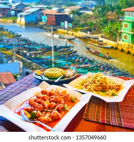 Best cafes of Nyaungshwe resort boast terraces on upper floors with a view on Inle Lake canal, canoes and the tasty dishes of Burmese cuisine - pork stew, banana wraps, rise noodles, Myanmar.