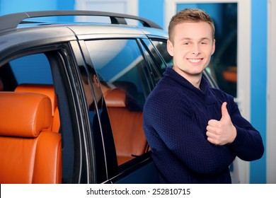It is the best car ever. Portrait of a handsome smiling man standing by his luxury car in the garage and showing his thumb up