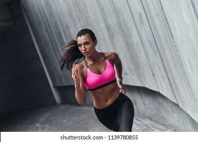 Best cardio ever. Modern young woman in sports clothing running while exercising outdoors
