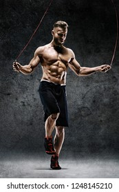 Best cardio workout. Young man skipping with a jump rope on dark background. Strength and motivation