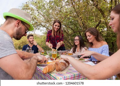 best cheerful friends have a picnic meal outdoors. they are eating salad cheese salami and bread and drinking rose wine