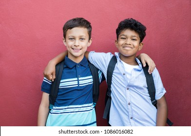 Best children friends standing with hand on shoulder against red background. Happy smiling classmates standing together on red wall. Portrait of multiethnic schoolboys enjoying friendship.