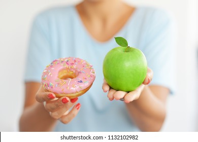 The best choice for a healthy lifestyle, between sweet and attractive doughnut and fresh green apple fruit