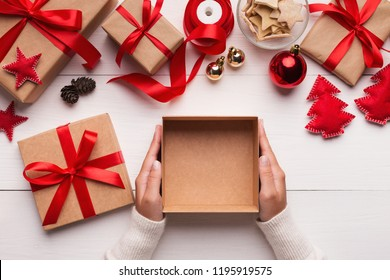 Best Christmas gift. Woman hands holding empty craft gift box, preparing surprise for holiday, top view, copy space