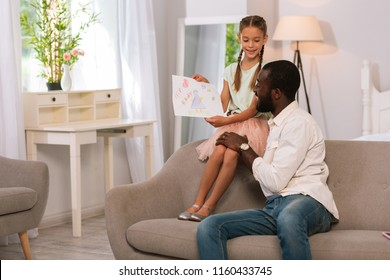 For the best dad. Delighted cute girl showing a drawing to her father while sitting with him on the sofa