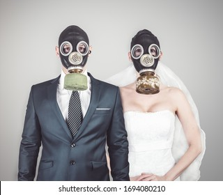 Best day of life. Wedding during the coronavirus period. Bride and groom in protective gas masks posing on a gray background. Style spring-summer 2020