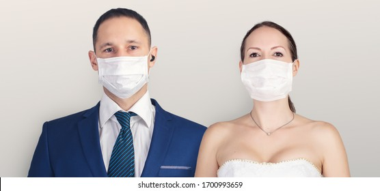 Best day of life. Wedding during the coronavirus period. Bride and groom in protective medical masks posing on a gray background